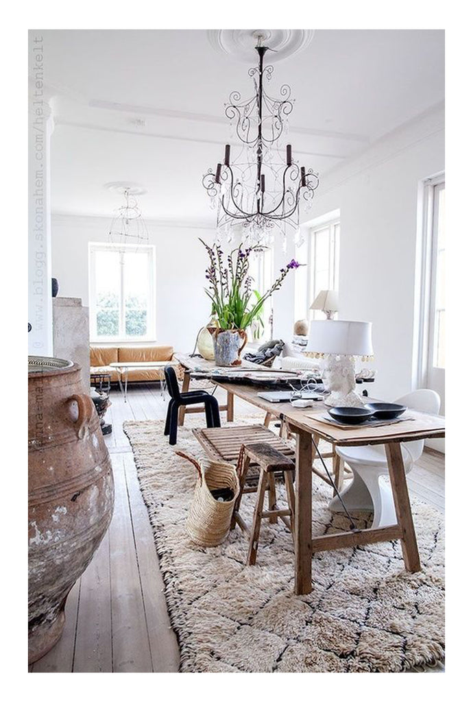 This rustic Danish country style dining room is a mix of vintage mid century modern design and traditional classic farmhouse elegance. An Italian chandelier, a long french workbench, oversized Moroccan ceramic urns, a sculptural chair and pink sofa. This room has all the elements of good interior design including a touch of the surprising and unexpected.