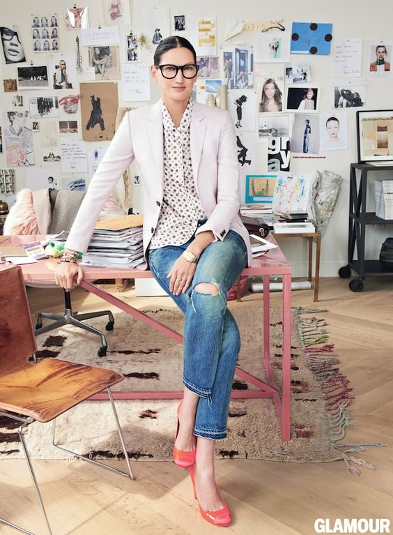 Jenna Lyon sit on her blush pink desk in coral pink heels. The abstract modern beni ourain is a balance to the moodboard collage in this iconic New York office.