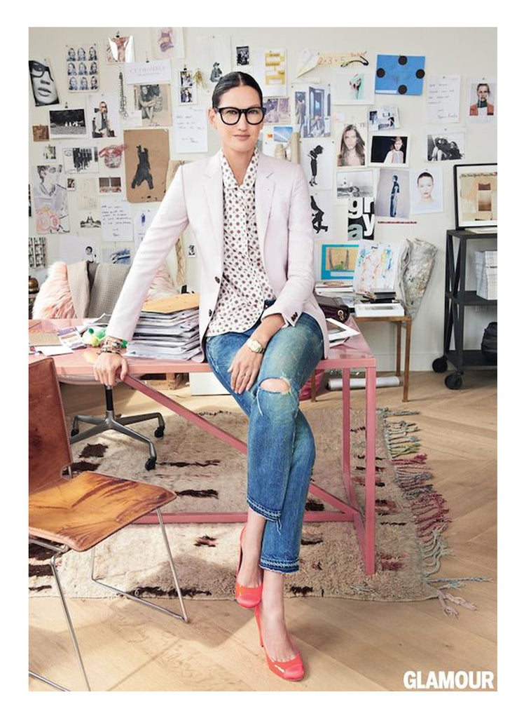 Jenna Lyon sits on her blush pink desk in a pale pink blazer and coral pink heels. The abstract modern beni ourain is a balance to the moodboard collage in this iconic New York office filled with an impressive collection of vintage mid century modern design collectibles. A mix of more masculine textures, iron, chrome, wood, and leather provides the contrast to a soft feminine color palette.