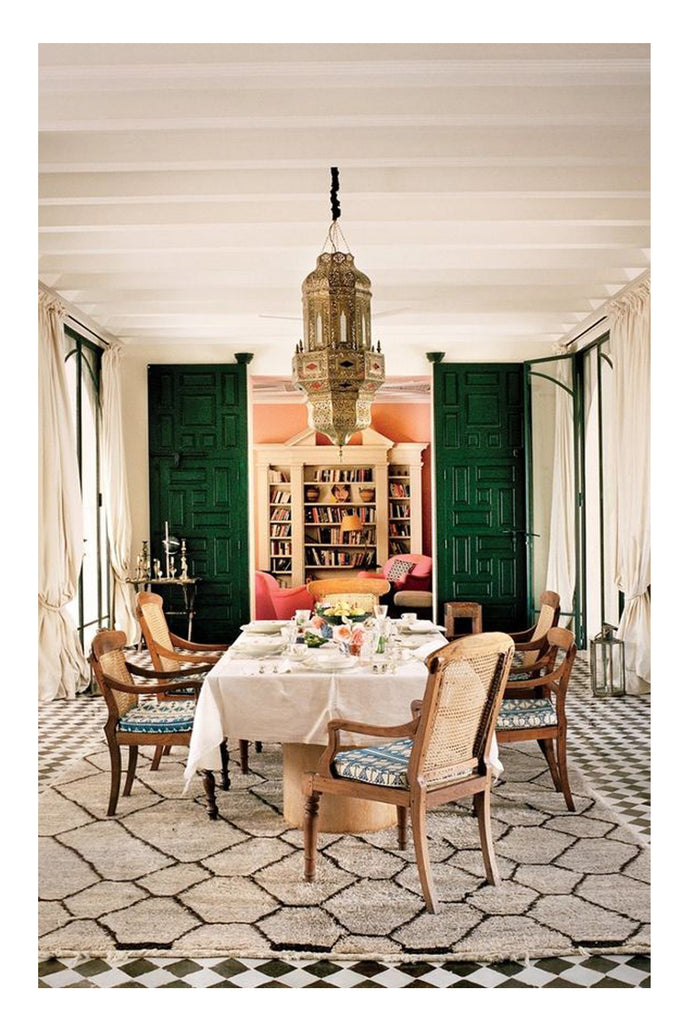 Fabulous, exotic dining is in the details of this trad-mod Moroccan inspired room, and a beautiful honeycomb pattern beni ourain sets the focal point for statement making interior design. A brass Moroccan artisan made pendant light hangs over an inviting table setting and classic traditional cane back dining chairs. But that beni ourain rugs makes the room.