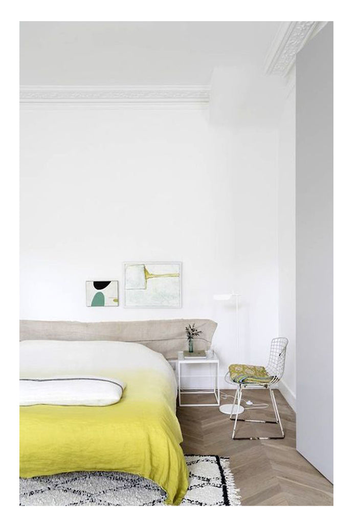 A cool collected London bedroom with a touch of whimsy features a beni ourain tucked behind a lime yellow duvet, a class mid century bertoia wire chair, and some curated abstract modern art.