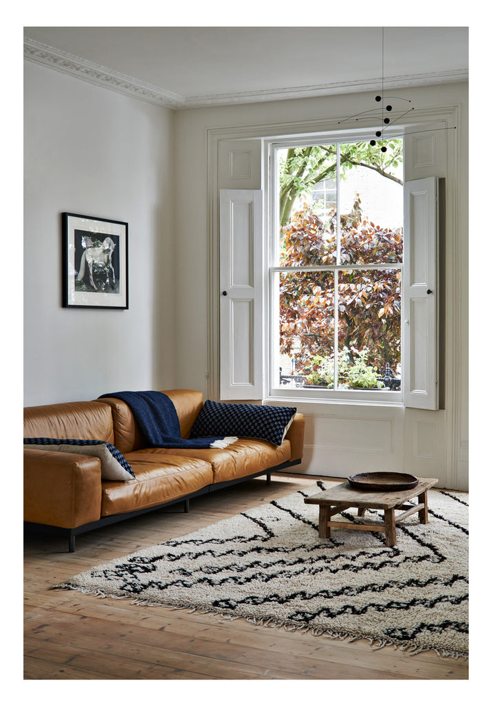 This clean lined minimalist sofa in cognac color leather elicits glamour and refinement. The sofa has an earthy and autumnal hue with a sense of richness and luxury, and when playful drama is added in the form of an unusual chevron patterned Beni Ourain rug, the resulting look is a mix of sumptuous and serene.