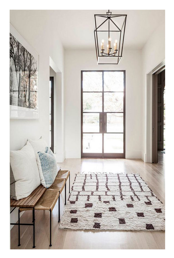 An arty unusual custom Beni Ourain rug sets the tone in a sparsely decorated entry, and highlights the French iron doors and gorgeous flood of light coming into the room. Such a strong focal point requires that the furnishing be more understated and simple, like a clean lined woven rush bench.