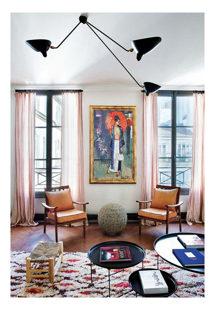 how to choose a rug: a Beni Ourain rug with pink accents anchors and elevates the design in a Parisian apartment that features an eclectic mix of vintage and contemporary furniture finds. The decidedly French furnishings sit off the rug, instead underneath a unique 60s original painting of a Geisha. High contrast drama takes the form of a graphic Moroccan berber rug and a Serge Mouille pendant light.
