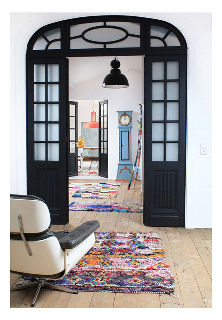 how to choose a rug: small vintage moroccan rugs are scattered on the floors of this Brooklyn New York townhome to add bright color to high contrast black white design. Decorating NY style with a Parisian twist.
