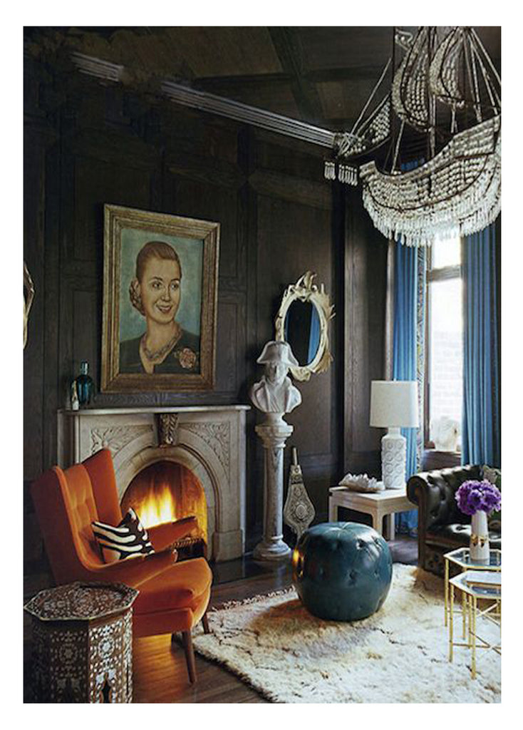 how to choose rug size: a dark, moody european living room that feature a vintage moroccan beni ourain, furniture placement method - front legs of furnishings placed on the small rug.
