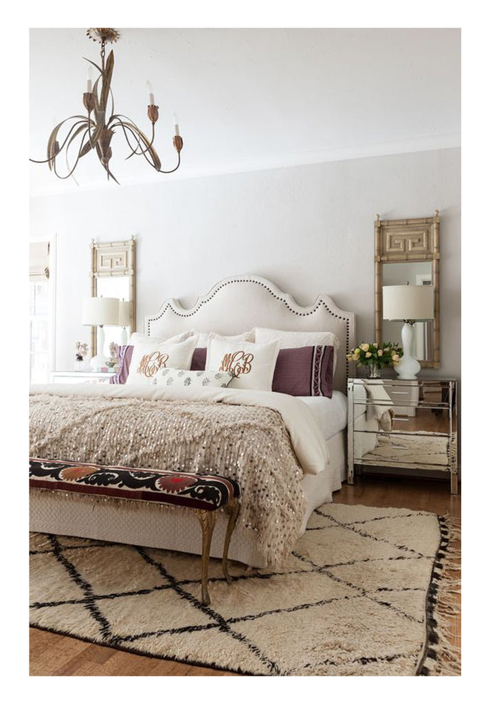 A gorgeous Beni Ourain with wide irregular diamond pattern makes the perfect statement in a traditional modern bedroom. This classic trad-mod look, with the curvy linen headboard and Italian leafy brass toleware chandelier might be incomplete without the striking Berber rug as the focal point.