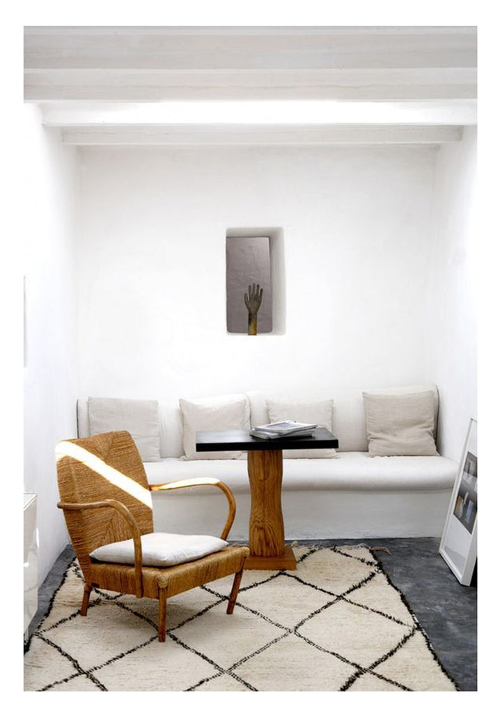 The architecture of this room looks precisely like that of Greek island homes on Oia and Mykonos. Stark white stucco walls, built in sofas, and natural fiber textures like this bentwood French modernist woven rush armchair are perfect for reminding us of days by the water. The classic Beni Ourain in a large scale pattern, the perfect compliment to mediterranean minimalism.