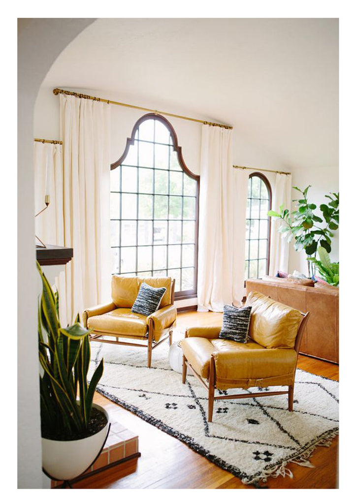 how to choose the right rug size: a custom moroccan beni ourain rug sits in front of the fireplace in a small yellow honey hued California living room furnished in blond leather and lots of light