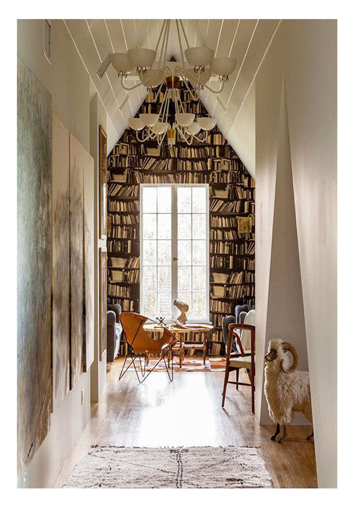 French windows and a floor to ceiling bookcase are the focal point of this stunning home library. The adjacent hallway features a plush Beni Ourain rug with chevron-like pattern - complement to the vintage leather bound circle chair - leading the way to a fresh take on a typically traditional space.