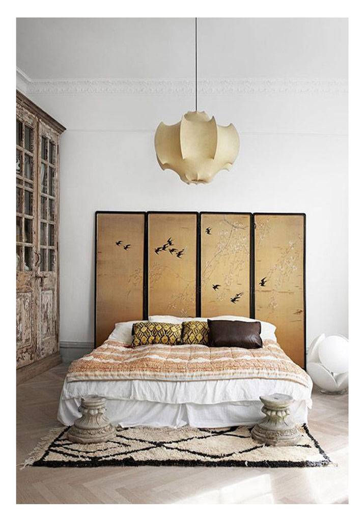 Beauty in the bedroom is the surprising mix of a silk chinoiserie divider screen as headboard and a bold, classic Beni Ourain rug. Add an oversized rustic French cupboard, some pretty Indian textiles, and a sculptural leather encased chandelier and the look is unexpected - glamorous and serene all at once.