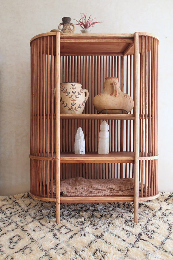 a curved spindle bookcase sitting on a large custom beni ourain rug at the gardener's house in marrakesh, morocco