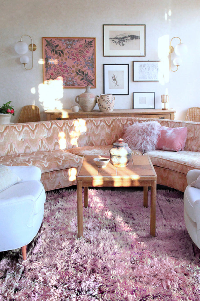 a living room with a blush pink beni mguild rug. Mid century modern design with a Moroccan twist.