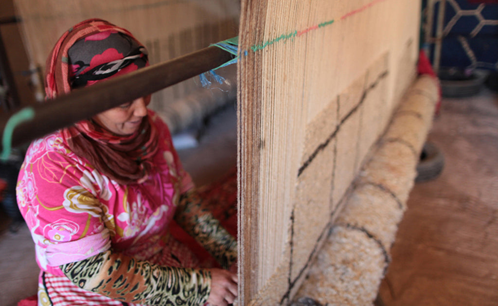 a moroccan woman works on a loom in the atlas mountains of morocco, making a custom made beni ourain rug