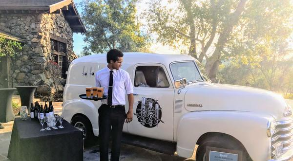 Black tie outdoor wedding event with white classic truck and draft beer.
