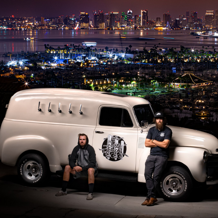 Young mobile bar service entrepreneurs with classic brown tap truck