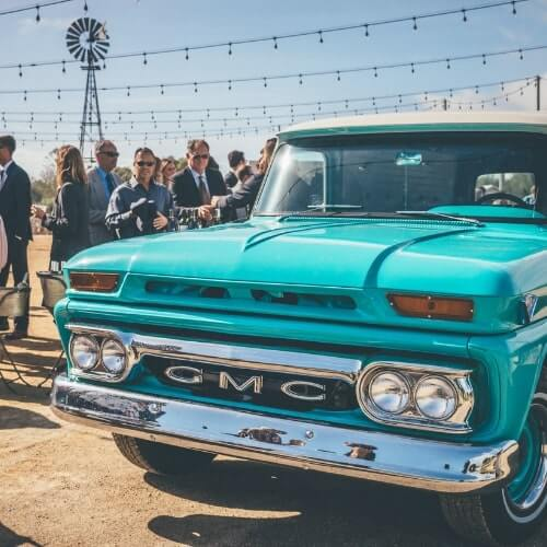 Blue GMC classic bar truck with event guests in the California desert
