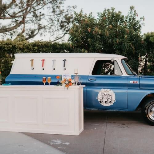 '65 Chevy Panel Truck. Blue bar truck serving outdoor wedding event with floral arrangements