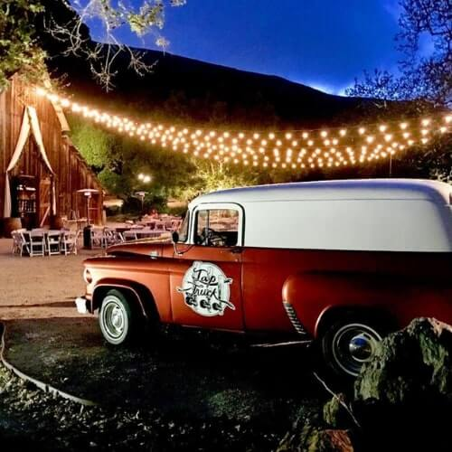 Red and white classic truck under lights at rustic barn wedding
