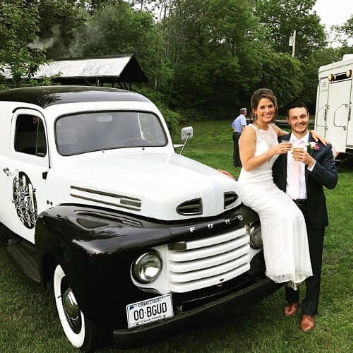 New England mobile bar truck with beautiful bride and groom at wedding in the countryside.