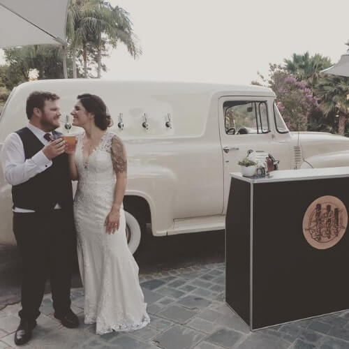 Classy event venue with vintage mobile bar truck and bride and groom