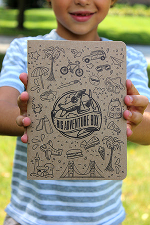 A boy is holding a custom Big Adventure Box journal. The age appropriate journal is meant to boost joy, empathy, happiness, as well as encourage the child to explore the world around him or her.