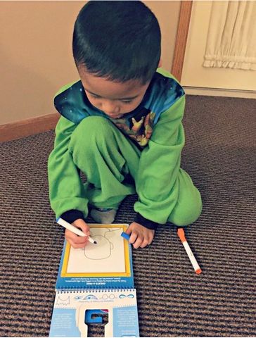 child drawing with activity book