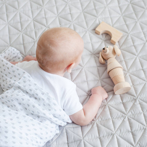 Baby playing on grey quilted mat.