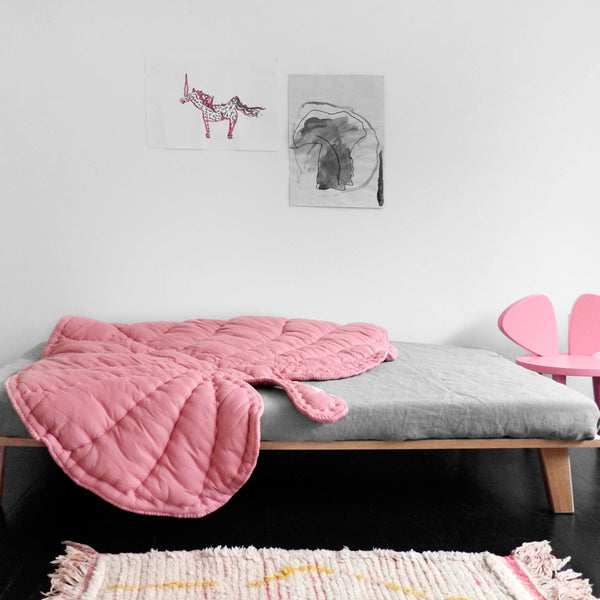 Rosa coloured leaf shaped blanket on bed.