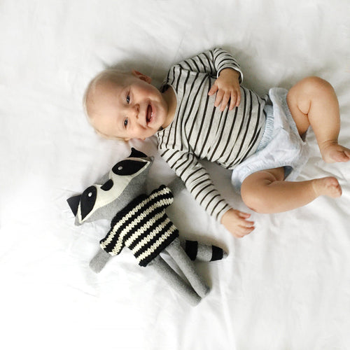 Raccoon soft toy next to baby