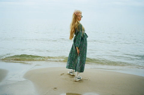 Lily wears a teal silk robe on a beach with sneakers