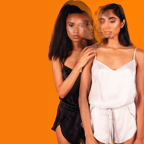 Kent Woman Silk Romper in Black and Cloud Gray, shown on two different models, front view, on orange background