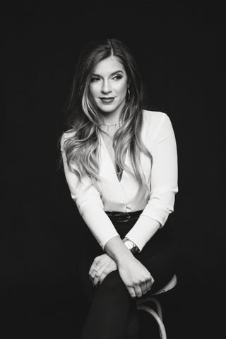 Black and white photo of Valentina, who is seated and smiling subtly with her wrists crossed casually