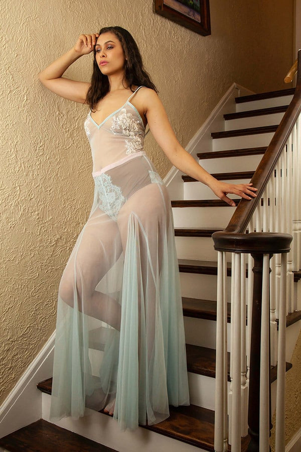 Model on stairs, with arm leaning on wall and hand lightly touching railing, wearing sheer tulle Thais Gown by Taryn Winters, in light blue with white and iridescent beaded appliqué on breasts.
