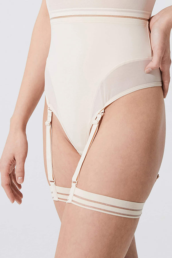 Opaak Lil leg strap garter in light beige (bleached sand), side/front view, on model