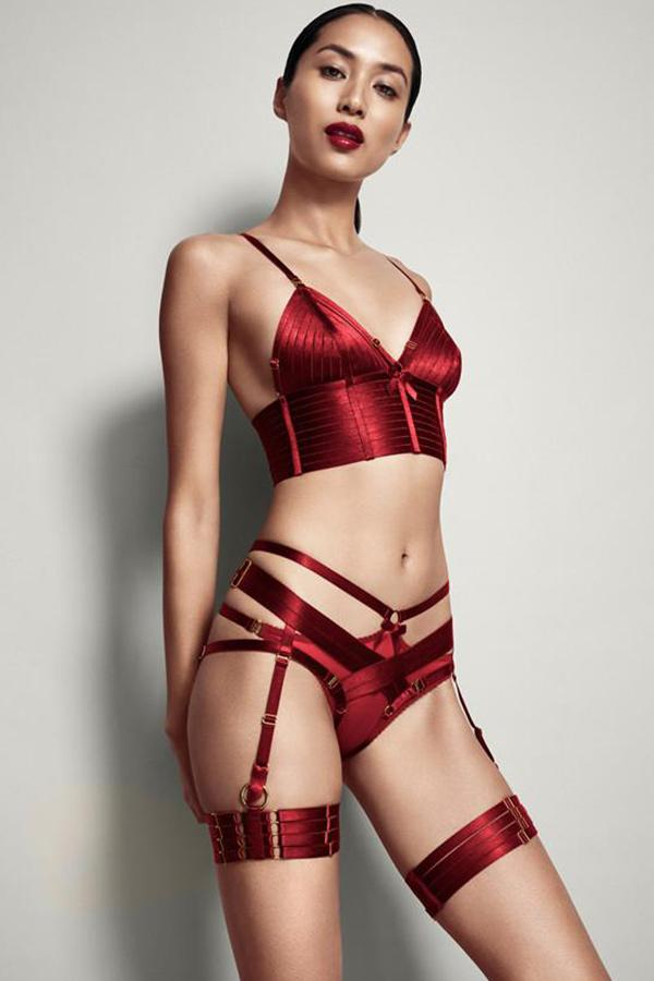 Bondage Belle Bordelle top in red, shown on model, side view, with matching harness thong, ouvert suspender brief and garters