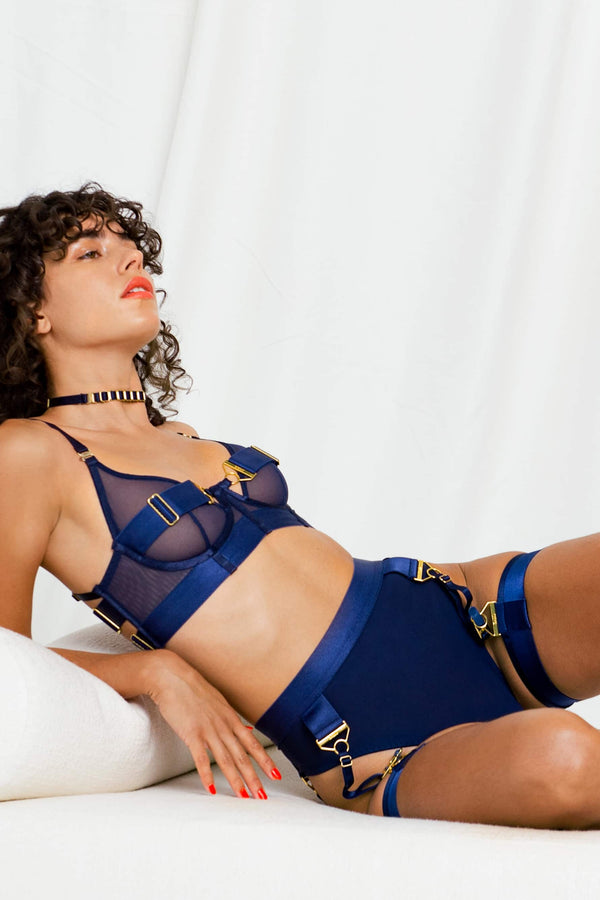 Bordelle Rey high waist thong with suspenders in navy blue, shown on model in matching garters and bra, front/side view