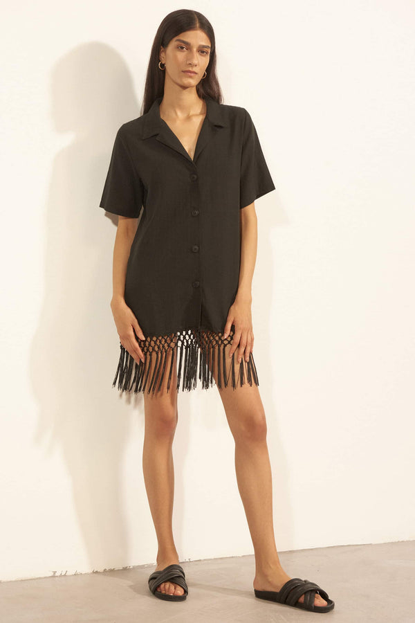 Else Cabo black cotton shirt dress with fringe hem, front view, on model
