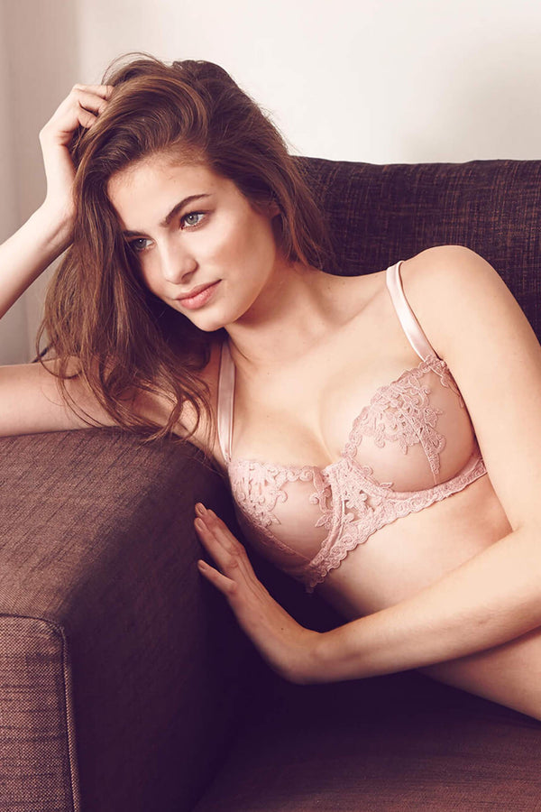 Affection light pink tulle and lace balcony bra by Fleur of England, on model lounging on couch, front view