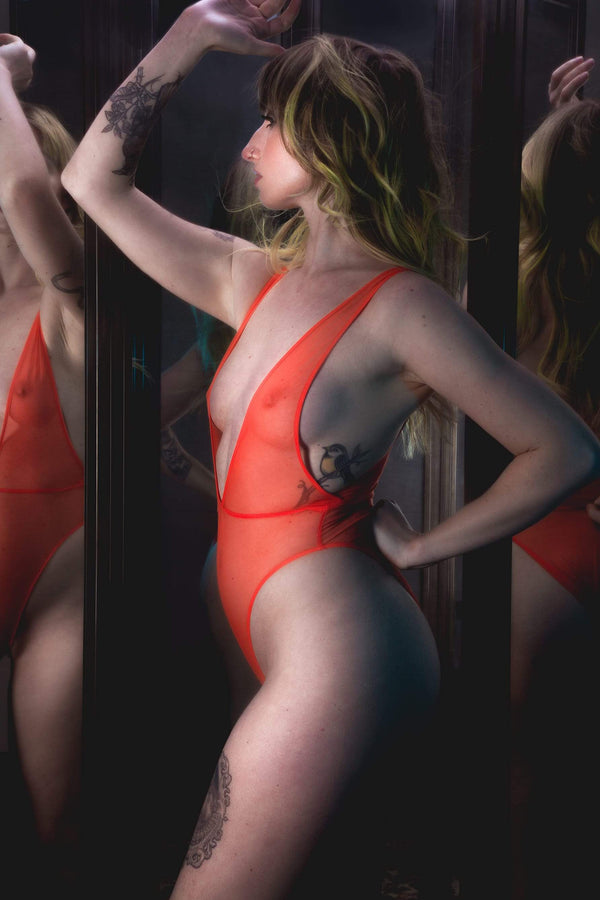 Only Hearts Wrestle Me sheer orange bodysuit. Shown on model, side view, showing high cut leg line ver her hip, and plunging neckline, hitting at her waistline, and the low sides. She's posed in front of a 3-way mirror with one arm on her back hip and the other folded with her thumb touching her forehead.