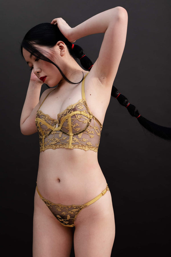 Yuna low rise Strap Knicker by Studio Pia, in black tulle and gold embroidery with gold silk trim. Front/side view on model.