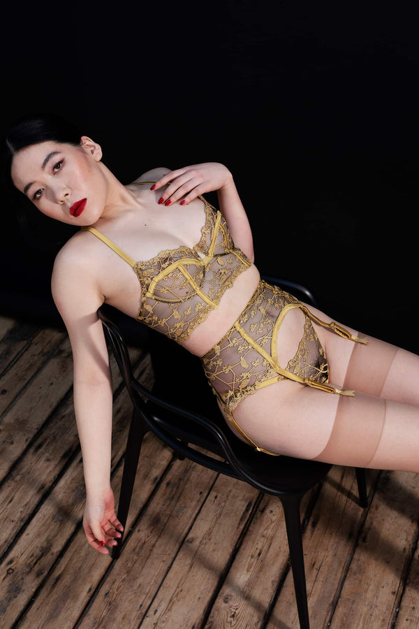 Yuna Suspender by Studio Pia in black tulle and golden embroidery with gold silk trim. Shown on model, front/side view.