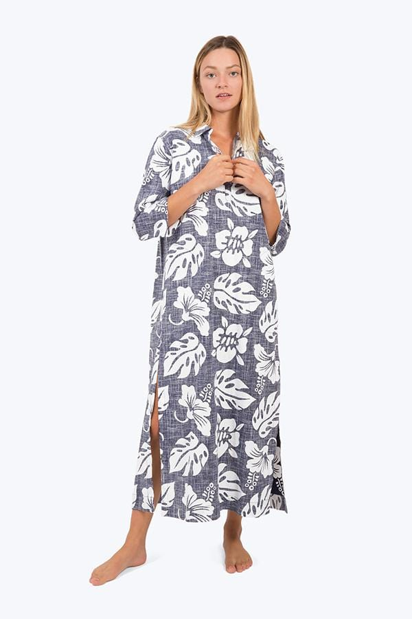 Sleepy Jones Celia Hawaiian print kaftan in denim blue and white. Shown on model with her hands at the collar, front view, showing the side slit just above the knee, and cropped sleeve length