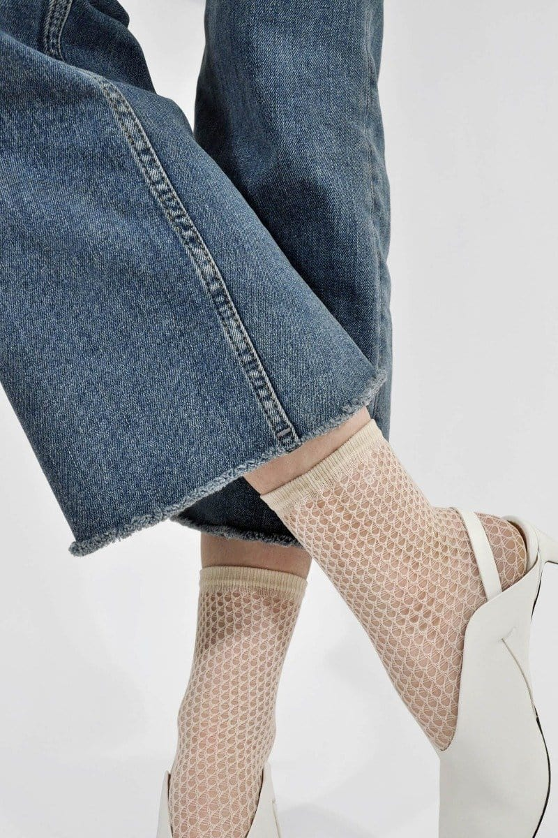 Ivory Vera Fishnet Sock by Swedish Stockings, shown on model, styled with cutoff jeans and white mules