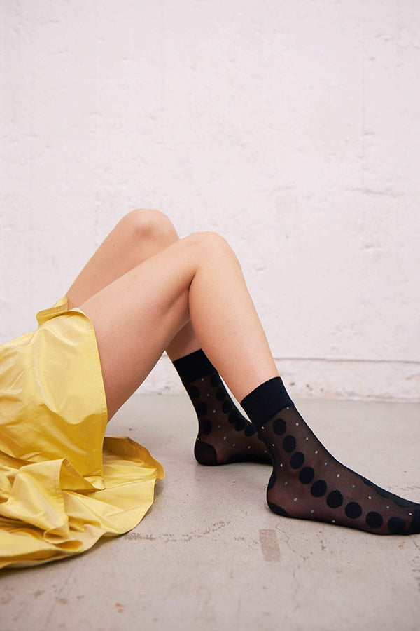 Swedish Stockings Viola Dot socks in black. Shown on model, who is laying on a concrete floor in a yellow dress with her legs bent and feet flat on floor. The cuff of the sock is just above her ankles, with a wide, opaque band. The rest of the sock is sheer with large black polka dots in vertical pattern, and small alternating white and light blue dots also in vertical pattern.
