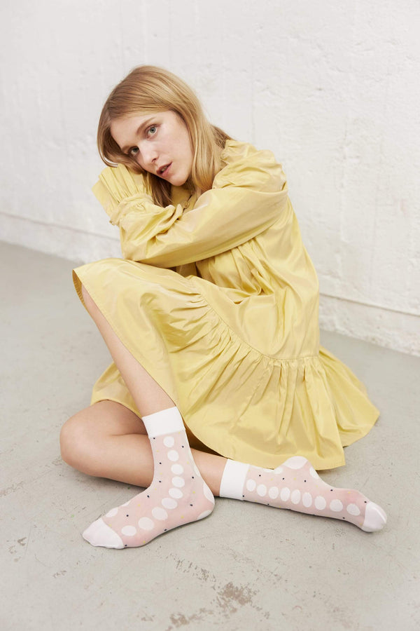 Swedish Stockings Viola Dot socks in Ivory, shown on model, who is in a yellow dress seated on a concrete floor. The Socks have a wide, opaque cuff that hits the model above the ankle, as well as reinforced toe & heel which we can see in the photo because her legs are sort of folded to show the front and sides of the socks. The pattern on the sheer white sock is large, opaque rows of white dots and tiny black & yellow dots in between.