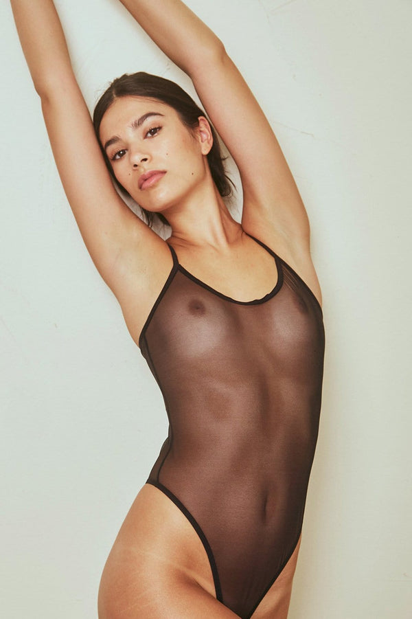 The Great Eros' Canova sheer black bodysuit, on model, with spaghetti strap shoulders, scoop neck and high cut leg