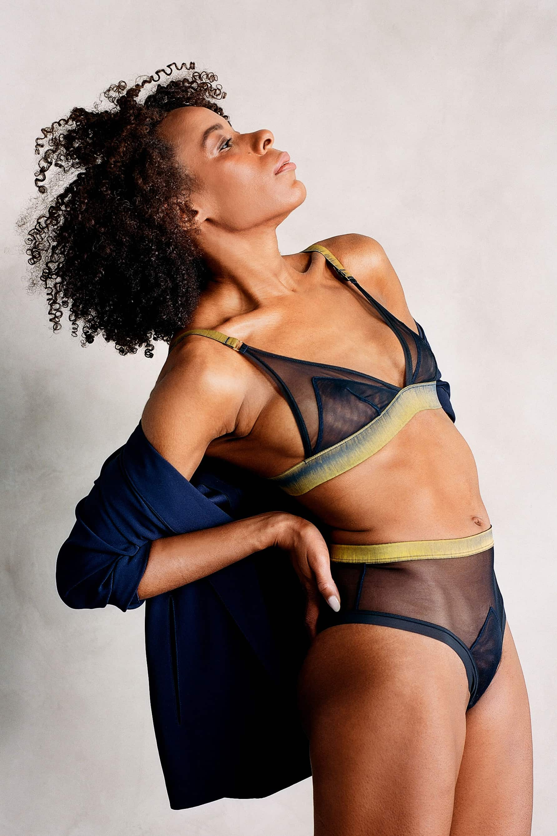 The Underargument Trust Your Gut triangle bra in midnight blue sheer tulle with mustard yellow trim, shown with matching high waist brief, side view on model