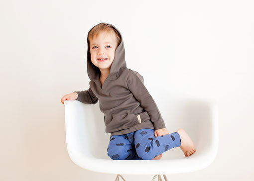 A young boy sits in a chair and models a gray hoodie and blue pants