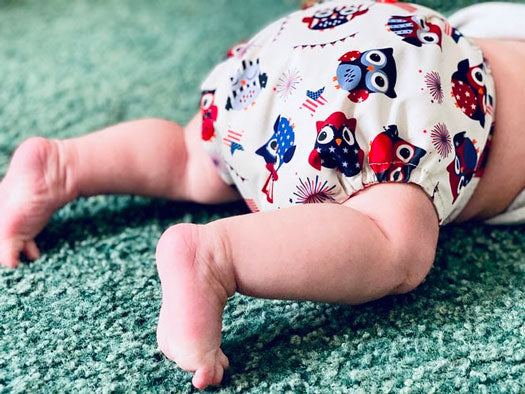 a baby wears a colorful cloth diaper